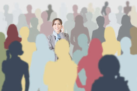 Confident Asian business woman using cellphone in a crowd, concept of female or business work. photo
