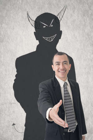 Concept of devil businessman with hand drawn evil shadow.
