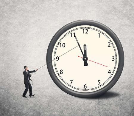 Hombre de negocios asiático tratando de volver el tiempo atrás, tirando de una cuerda atada a las manecillas de un reloj.