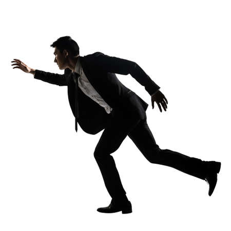 Silhouette of Asian business man running, full length portrait isolated on white. Side view. photo