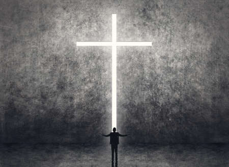 Silhouette of businessman stand in front of the cross light on the wall. photo