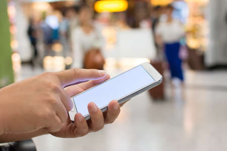 consumers: Using smartphone in a market or department store, closeup image.