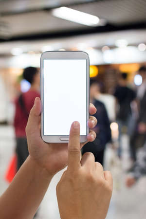 retail display: Using smartphone in a market or department store, closeup image.