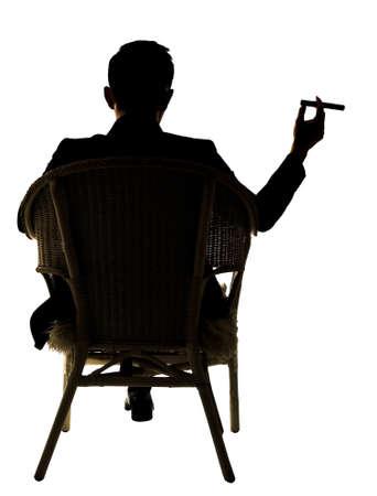 Silueta de hombre de negocios se sienta en silla y mantenga un cigarro, retrato de cuerpo entero sobre fondo blanco. Foto de archivo