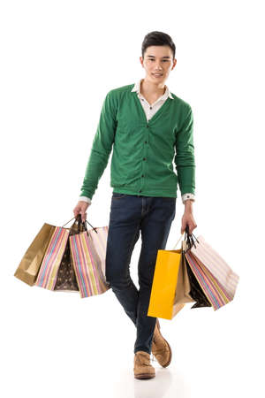 Young Asian man shopping and holding bags, full length portrait isolated on white background.