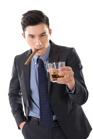 Asian young business guy with a cigar and hold a glass of whisky looking at you. photo