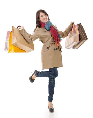 Winter shopping woman of Asian holding bags, full length portrait isolated on white background. photo
