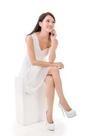 Belleza asiática joven atractiva en vestido de blanco sentado en una caja, retrato de cuerpo entero aislados en blanco.