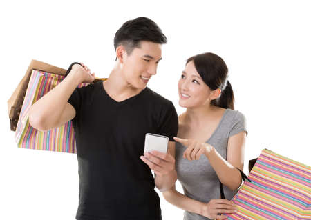 Attractive young Asian couple shopping and looking at cellphone, full length portrait isolated on white background.