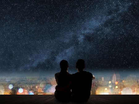 젊은 아시아 부부의 실루엣 별이 도시 위의 나무 바닥에 앉아있다. 스톡 콘텐츠