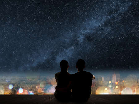 Silhouette of young Asian couple sit on wooden ground above the city under stars. Фото со стока