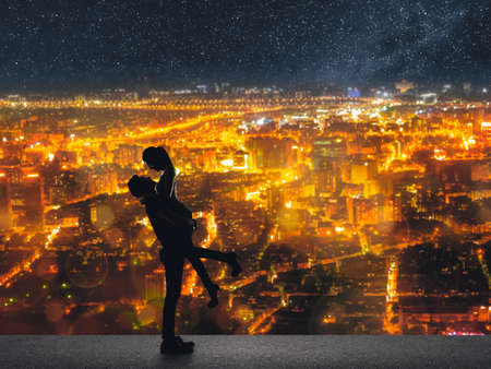 Silhouette of Asian couple, man hold his girlfriend up above the city in night under stars. photo