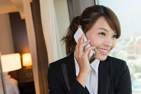 Asian young business woman using cellphone, closeup portrait in hotel. photo