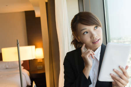 consider: Asian business woman using tablet and thinking, closeup portrait in hotel room.