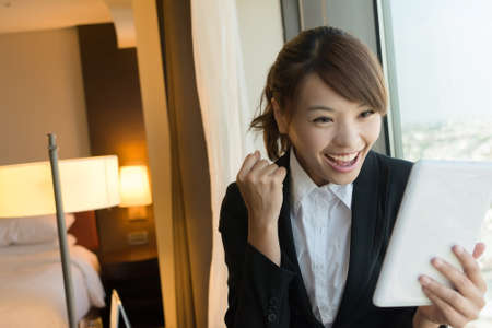 touch screen phone: Cheerful Asian business woman using tablet, closeup portrait in hotel room.