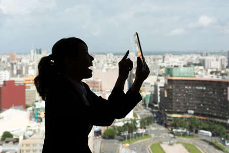 Silhouette of Asian business woman using tablet in a room, concept of technology or communication. photo