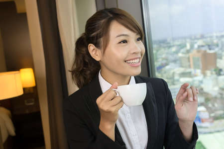 Asian business woman holding a cup of coffee and looking into distance near the window in hotel room. photo