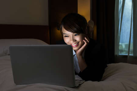 Asian business woman working on bed with laptop in hotel at night. photo