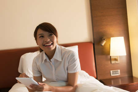 Business woman using laptop on the bed in hotel at the morning. photo