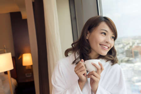 woman bathrobe: Asian woman holding a cup of coffee in the morning.