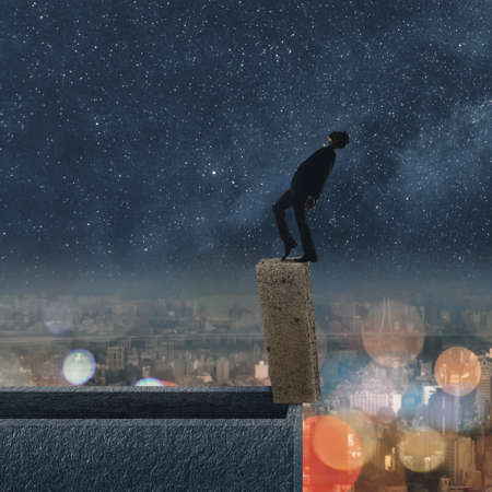 Concept of dangerous balance, business man dancing on a stone of the roof of city under stars in night. photo