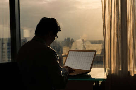 Rear view of Asian businessman working at sunset in office. photo