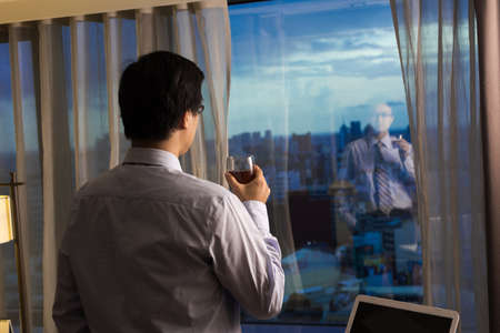 asian businessman: Asian businessman take a cup of coffee and looking into the distance, concept of traveling business, dream, work at night etc.