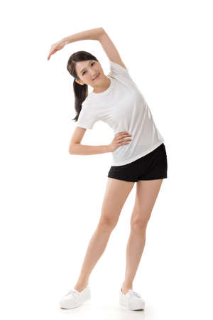 Fitness asian girl doing stretch exercise. Full length portrait isolated on the white background.