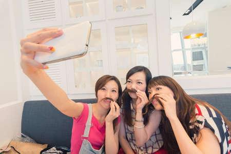Happy smiling Asian women selfie in a restaurant.