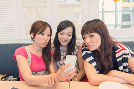 Asian lady in the restaurant and share something in mobile phone with her friends. photo