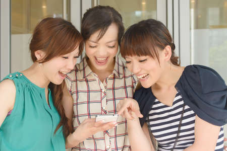 Group of smiling Asian women looking at something on a cellphone.