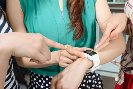Asian woman using wearable watch and showing to her friends. Stock Photo