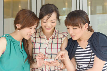 Group of smiling Asian women looking at something on a cellphone. photo