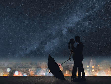 Silhouette of couple hug under stars.