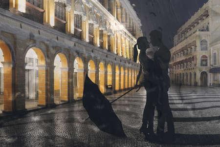 uomo sotto la pioggia: Coppia in piedi nella strada piove di notte. Mostra immagine attraverso la finestra con acqua.