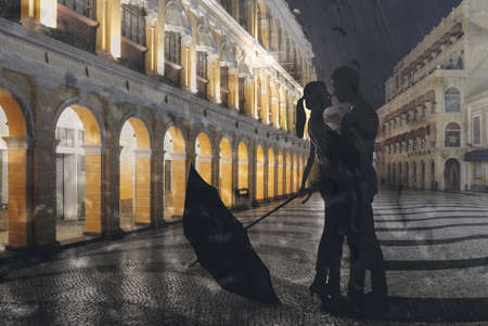 Couple standing in the raining street in the night. Show image through the window with water.
