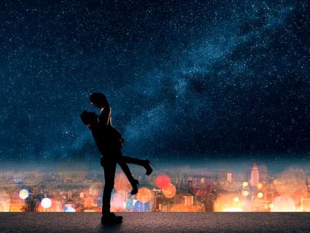 浪漫: 亞洲夫婦的剪影,男子抱女友了上文明星城市的夜晚。 版權商用圖片