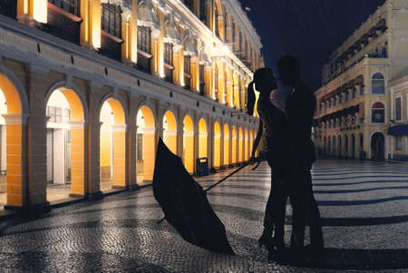 Couple standing in the raining street in the night. Banco de Imagens