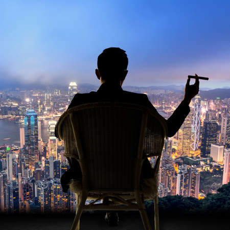 Silhouette of businessman sit on chair and hold a cigar, looking the harbor of Victoria at Hong Kong, Asia. photo