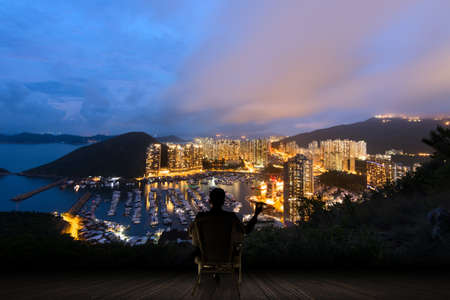 Silhouette of businessman sit on chair and hold a cigar and looking at the skyscrapers and harbor in Aberdeen, Hong Kong, Asia. Stock Photo