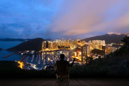 Silueta del hombre de negocios se sienta en silla y mantenga un cigarro y mirando a los rascacielos y el puerto de Aberdeen, Hong Kong, Asia. Foto de archivo