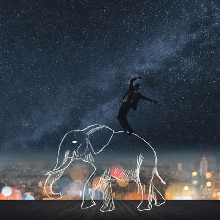 Business man dancing on the elephants back under the stars. photo