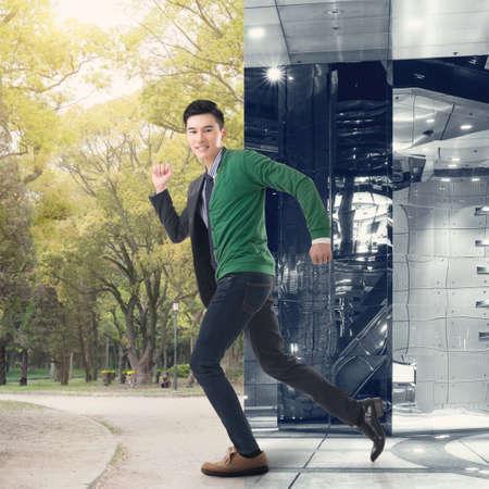 Asian junger Mann Flucht aus der modernen Büro zum park. Konzept der Freiheit, der Balance, der Arbeit.
