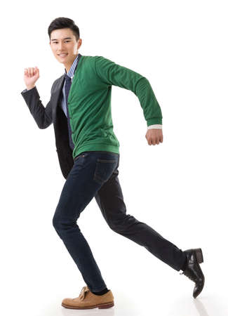 Asian young man running with casual clothes mix business suit, concept of life and work balance. photo