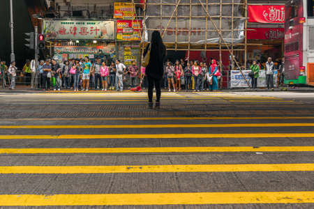 cross road: HONG KONG - MAY 11, 2014: Pedestrians wait to cross the street in the district of Mong Kok in Hong Kong. Mong Kok is one of the most crowded district in the world.