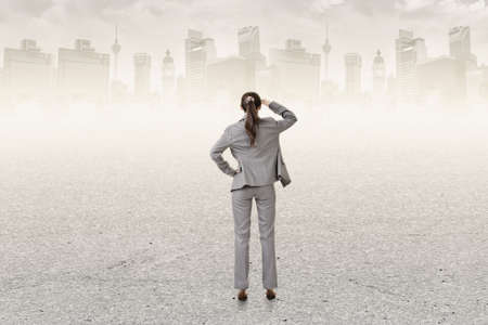 back ground: Concept of success with businesswoman standing on the ground and looking ahead for the opportunities. Rear view. Stock Photo