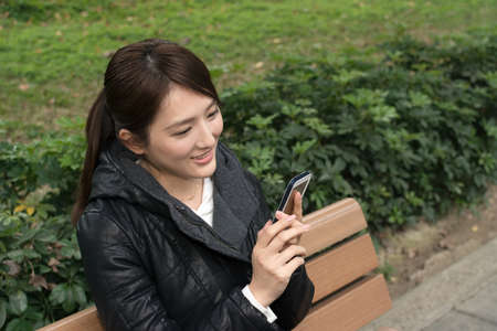 hp: Attractive young Asian woman using smartphone, closeup portrait. Stock Photo