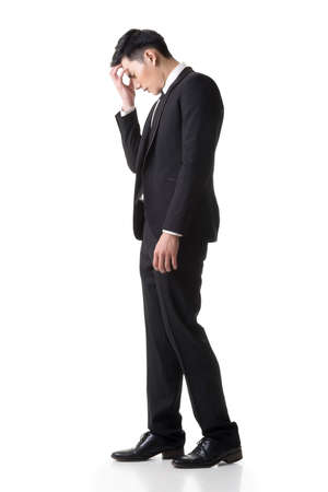 Regret young business man standing and thinking, full length portrait isolated on white background. Stock Photo