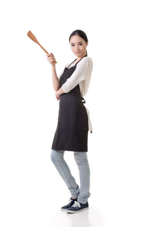 Young Asian housewife hold a spatula in apron, full portrait isolated on white background. Stok Fotoğraf