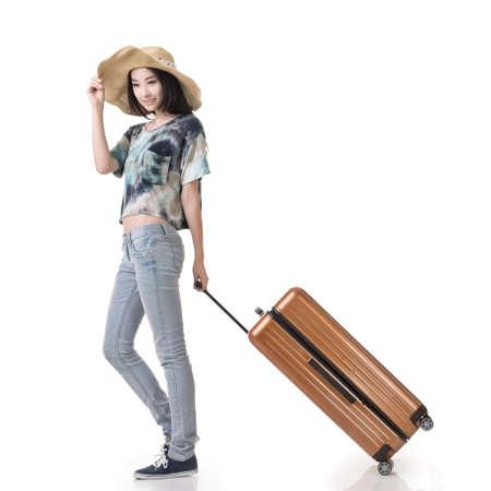 흥미로운 아시아 여자는 가방, 흰색 배경에 고립 된 전체 길이 초상화를 드래그합니다. 스톡 콘텐츠